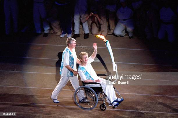 Torchbearers Betty Cuthbert is pushed by Raelene Boyle during the Opening Ceremony of the Sydney 2000 Olympic Games at the Olympic Stadium in...