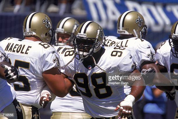 Willie Whitehead of the New Orleans Saints grips onto Chris Naeole in a warm up practice before a game against the San Diego Chargers at Qualcomm...