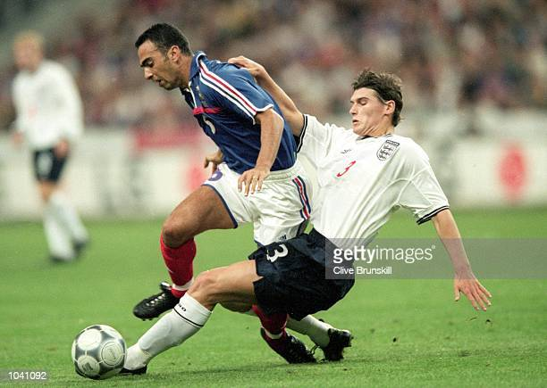 Youri Djorkaeff of France is tackled by Gareth Barry of England during the International friendly match at the Stade de France in Paris France The...