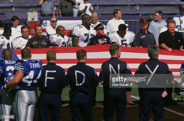An American Flag is held in memory of 9/11 as the National Anthem is sung during opening cerimonies before the game between the Philadelphia Eagles...