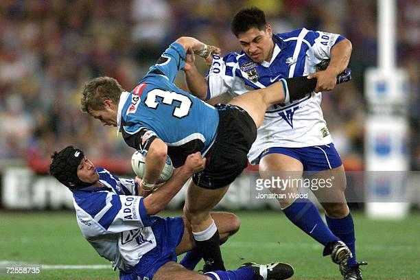 Andrew Emelio of the Sharks is tackled by the Bulldogs defence during the NRL Jersey Flegg Grand Final between the Bulldogs and the Sharks held at...