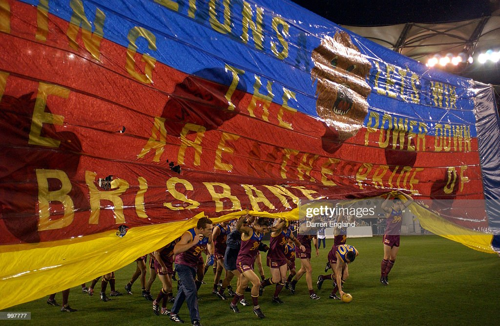 Brisbane Lions players run thru the team banner before the AFL Qualifying final match between the Brisbane Lions and the Port Adelaide Power played at the Gabba in Brisbane, Australia. DIGITAL IMAGE. Mandatory Credit: Darren England/ALLSPORT