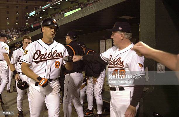 Cal Ripken Jr. #8 of the Baltimore Orioles is congratulated by teammates and coach Terry Crowley after Ripken hit a sacrifice fly to score Chris...