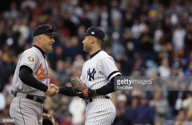 Cal Ripken Jr of the Baltimore Orioles shakes hands with Derek Jeter of the New York Yankees before the game at Yankee Stadium in the Bronx New York...