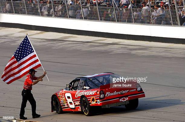 Dale Earnhardt Jr is given an American flag by one of his crew members as he prepares to do a victory lap in his Budweiser Cheverolet Monte Carlo...