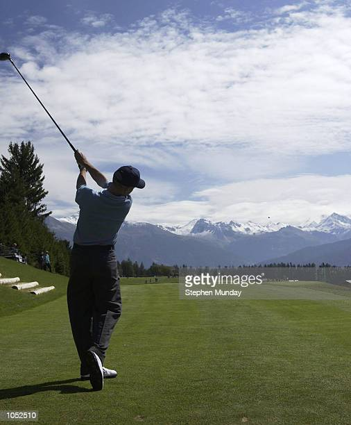 Dean Robertson of Scotland plays his tee shot on the 330 yard par four 7th hole towards snowcapped mountains in the Alpine valley during the first...