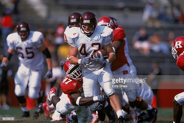 Doug Easlick of the Virginia Tech Hokies moves with the ball as Tarell Freeney of the Rutgers Scarlet Knights dives to grab his leg during the game...