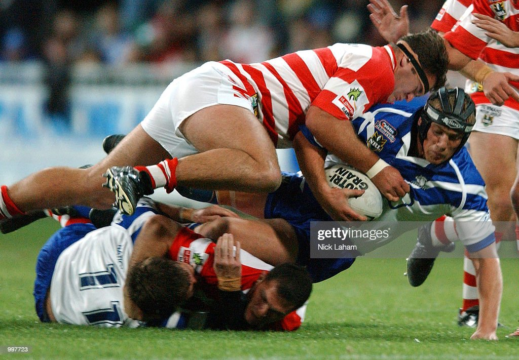 Jamie Feeney #14 of the Bulldogs is tackled by the Dragons defence during the NRL qualifying final between the Bulldogs and the St George Illawarra Dragons held at the Sydney Showground, Homebush Bay, Sydney, Australia. DIGITAL IMAGE Mandatory Credit: Nick Laham/ALLSPORT