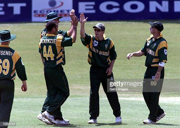 Jonty Rhodes congratulates Charl Langeveldt both of South Africa, on getting the wicket of Henry Olonga during the one day match played between South...