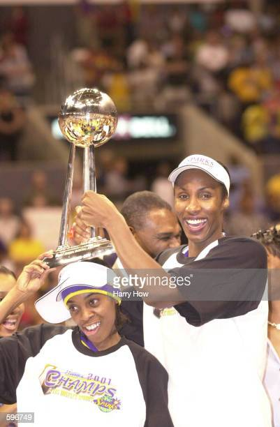 Lisa Leslie of the Los Angeles Sparks holds the 2001 Championship trophy with teammate Nicky McCrimmon after defeating the Charlotte Sting in game...