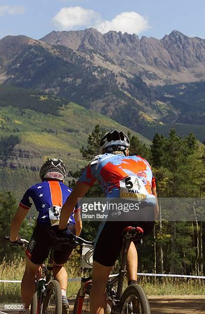 Matt Hawkins of the USA and Dylan Sebel of Canada bike with a view of the Gore Range during the under23 men's cross country competition of the UCI...