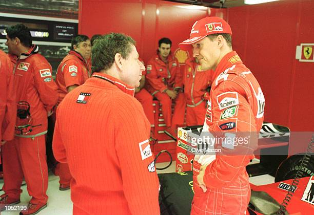 Michael Schumacher of Germany and Ferrari chats to technical director Jean Todt while they await the start of the morning session which was delayed...