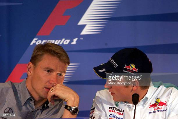 Mika Hakinnen of Finland talks to the driver who will take his seat at McLaren next year Kimi Raikkonen at the press conference for the US grand prix...
