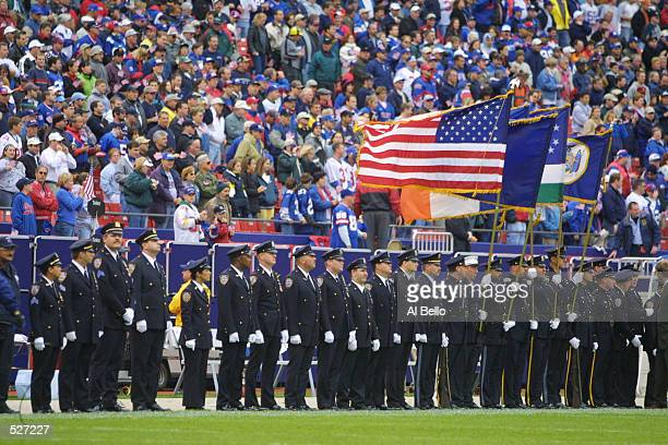 New York firemen and police line up on the field before the game between the New York Giants and New Orleans Saints at Giants Stadium in East...