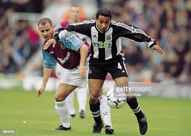 Nolberto Solano of Newcastle United holds the ball up against Laurent Courtois of West Ham United during the FA Barclaycard Premiership match played...