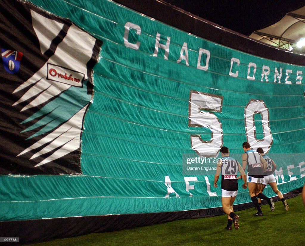 Port Adelaide players run thru the team banner before the AFL Qualifying final match between the Brisbane Lions and the Port Adelaide Power played at the Gabba in Brisbane, Australia. DIGITAL IMAGE. Mandatory Credit: Darren England/ALLSPORT