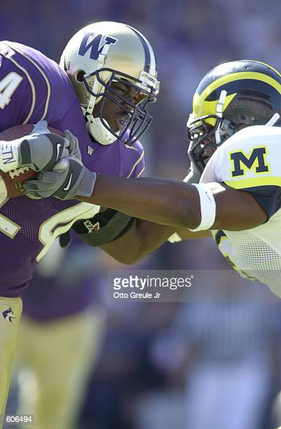 Rich Alexis of the Washington Huskies fights for yards against Victor Hobson of the Michigan Wolverines during the game at Husky Stadium in Seattle...