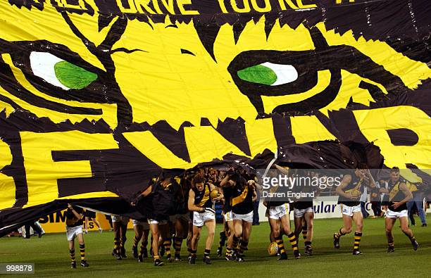 Richmond players run thru their banner at the start of the match against Brisbane during the AFL second Preliminary Final between the Brisbane Lions...