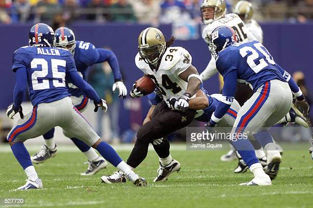Ricky Williams of the New Orleans Saints in action against the defense of Will Allen and Sam Garnes of the New York Giants during the game at the...