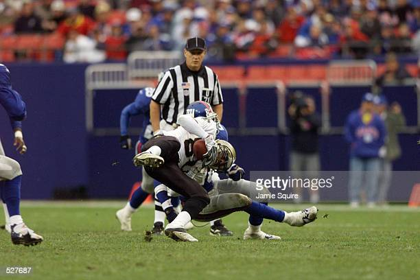 Robert Wilson of the New Orleans Saints is tackled by Sam Garnes of the New York Giants during the game at the Meadowlands in East Rutherford New...