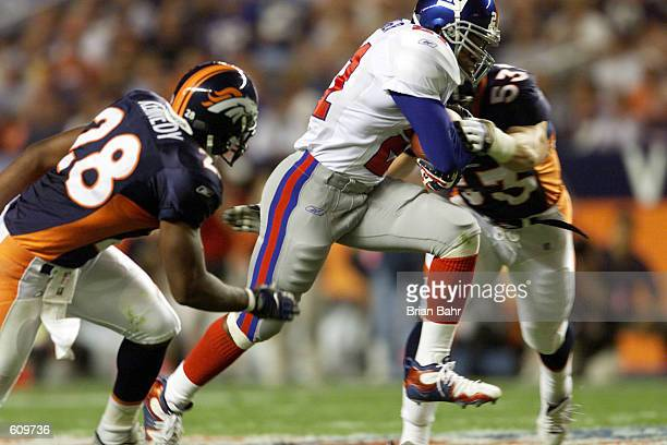 Running back Tiki Barber of the New York Giants barges downfield against Bill Romanowski and safety Kenoy Kennedy of the Denver Broncos The Broncos...