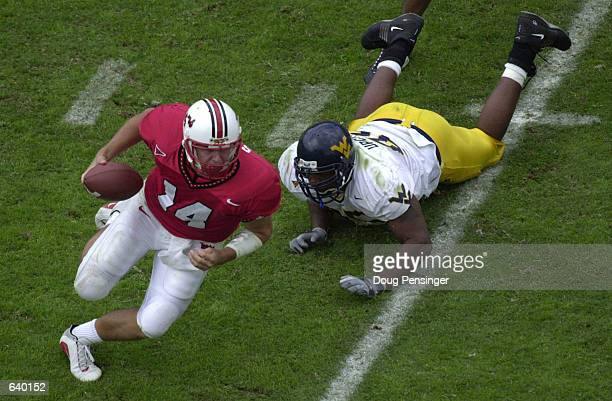 Shaun Hill quarterback of the Maryland Terrapins eludes a tackle by David Upchurch of the West Virginia University Mountaineers at Byrd Stadium on...