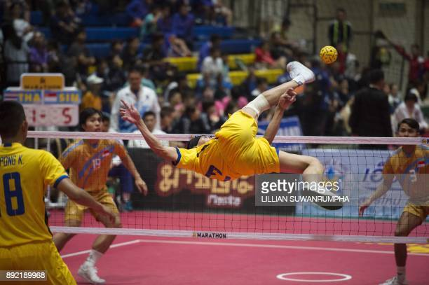 A sepak takraw player from Thailand roll spikes the ball over the net against Singapore during the King's Cup Sepaktakraw World Championship in...