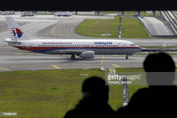 A couple watches a Malaysia Airlines Boeing 737 passing in front of the observation deck of the Kuala Lumpur International Airport in Sepang 26...