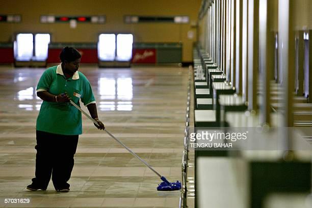 A janitorial services worker cleans the floor area in front of Air Asia checkin counters at the newlybuilt Low Cost Carrier Terminal at the Kuala...