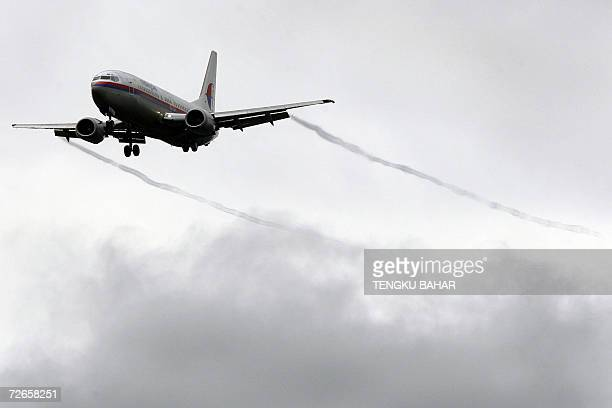 A Malaysia Airlines Boeing 737 aircraft leaves vapour contrails after flying through lowaltitude clouds while making its final approach at the Kuala...