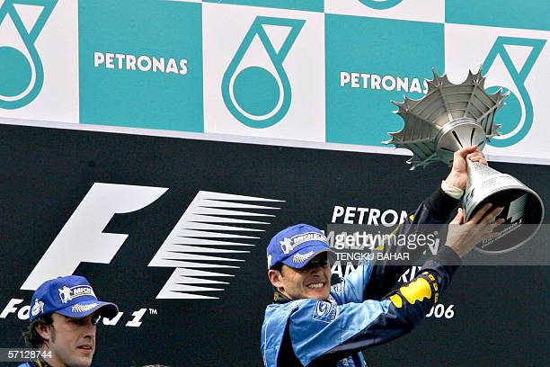 Italian F1 driver Giancarlo Fisichella of Renault lifts his Malaysian F1 Grand Prix winner's trophy while teammate Spaniard Fernando Alonso who took...