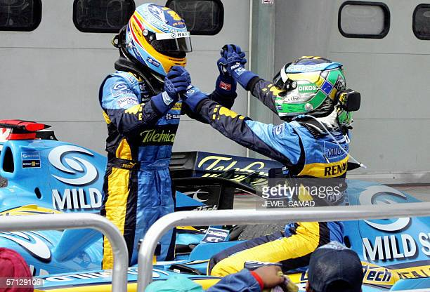 Italian Formula One driver Giancarlo Fisichella is congratulated by his second placed teammate Spanish Fernando Alonso at the endo of the Malaysian...