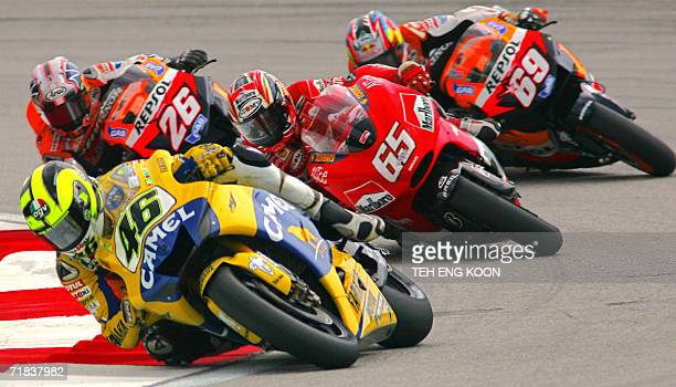 Italian motocycle rider Valentino Rossi takes a turn followed by his countryman Loris Capirossi , Spanish motorcycle rider Dani Pedrosa and US...