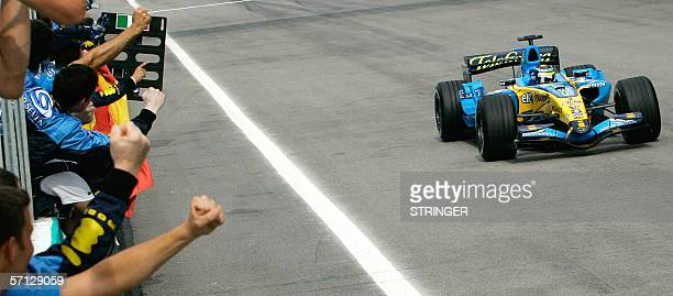 Renault Formula One driver Giancarlo Fisichella of Italy waves to his team members after crossing the finishing line of the Malaysian F1 Grand Prix...