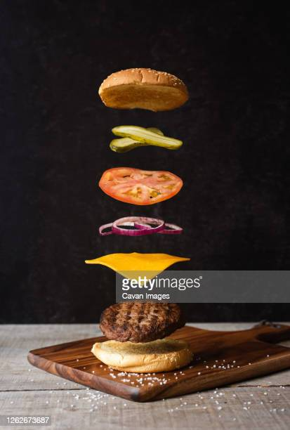 separated burger with floating ingredients on black background. - hamburger stock pictures, royalty-free photos & images