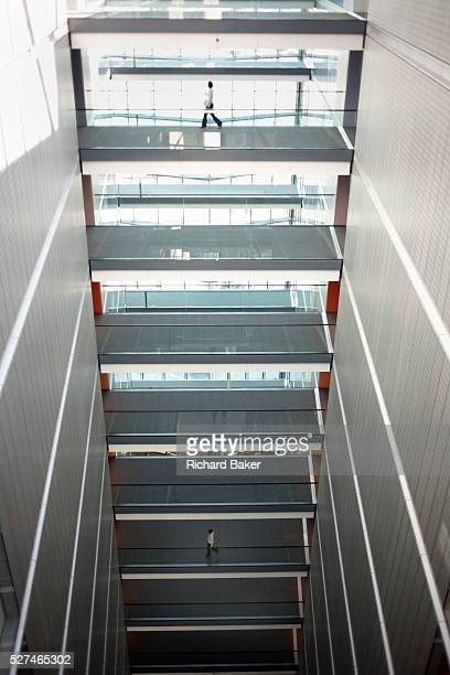 Separated by four floors, two employees of the auditing company Ernst & Young, make their way along walkways in the main atrium of E & Y's European...