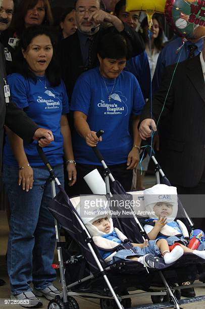Separated twins Clarence and Carl Aguirre sit in a double stroller as their mother Arlene and grandmother Evelyn wheel them from Montefiore Medical...