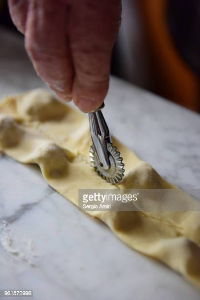 Separating pasta parcels using a pasta cutter wheel to make tortellini