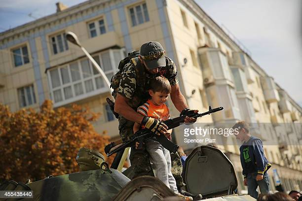 A separatist soldier shows a child a gun during a city celebration in Lugansk on September 14 2014 in Lugansk Ukraine Lugansk a separatist held city...