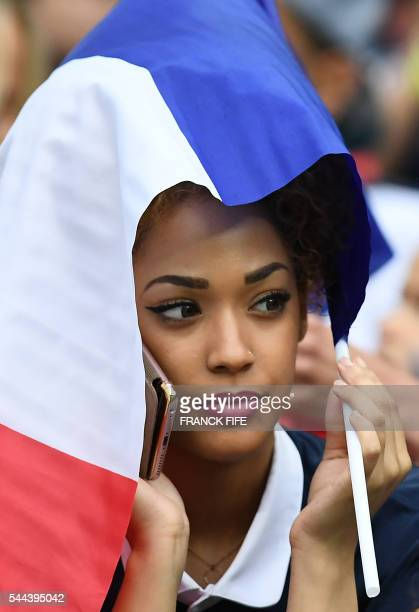 Sephora Coman wife of France's forward Kingsley Coman protects her hair with the French flag prior to the start of the Euro 2016 quarterfinal...