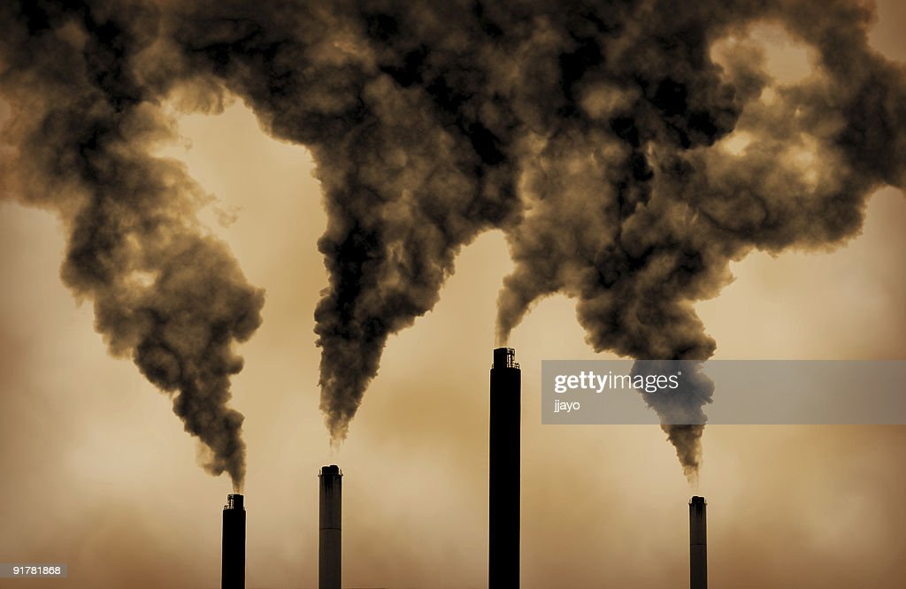 Sepia image of smoke coming from tall industrial chimneys : Stock Photo