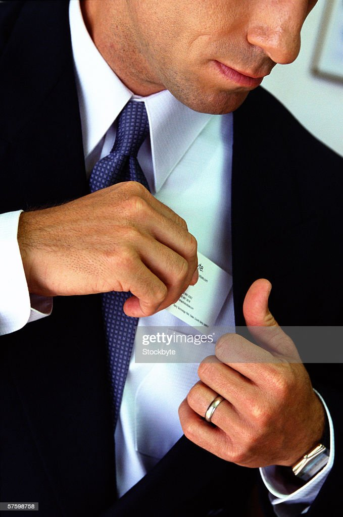 sepia shot of business man inserting a credit card into his shirt pocket : Stock Photo