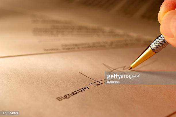 sepia toned image of signing a contract with light rays - deed stock photos and pictures