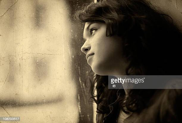 Sepia Toned Portrait of Pensive Young Woman Looking Out Window