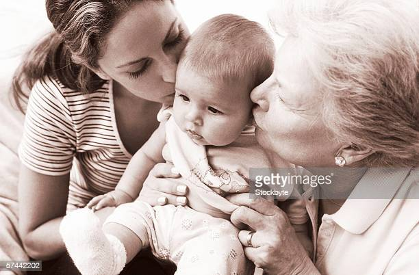 sepia toned view of a baby with the mother and grandmother kissing him
