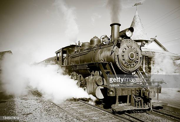 sepia toned vintage steam engine locomotive train leaving station - locomotive stock photos and pictures