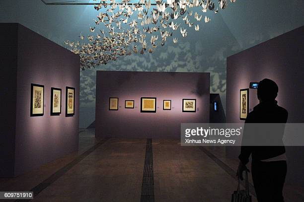 A reporter takes photos of the works of MC Escher during a media preview at Singapore's Marina Bay Sands ArtScience Museum Sept 22 2016 The exhbition...