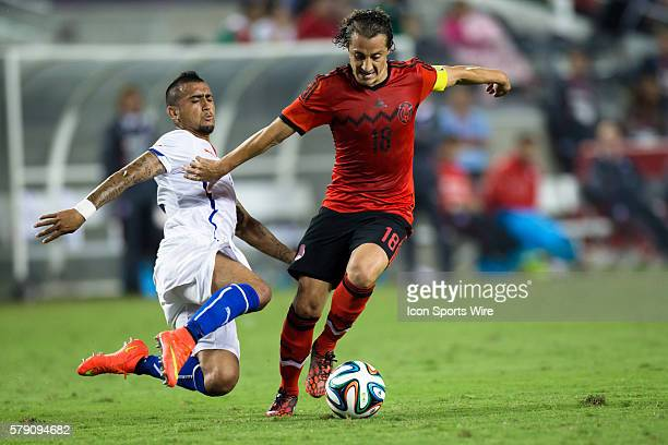 Chile midfielder Arturo Vidal tackles Mexico midfielder Andres Guardado during the game between Mexico and Chile at Levi's Stadium in Santa Clara...