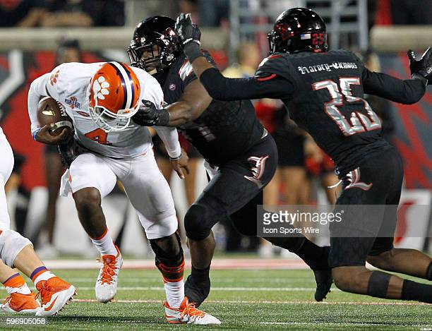 Clemson Tigers quarterback Deshaun Watson fights to break free from Louisville Cardinals' Sheldon Rankins during the second half of play at Papa...