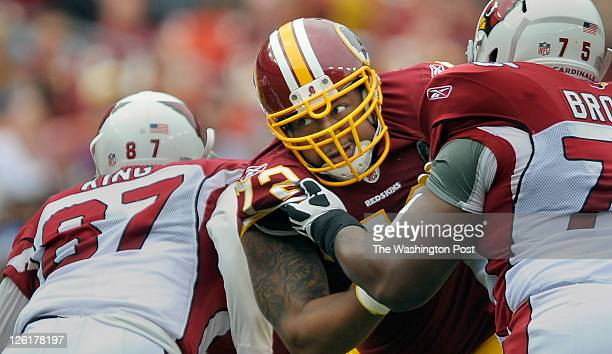Washington Redskins defensive end Stephen Bowen center takes on Cardinals tight end Jeff King left and Cardinals offensive tackle Levi Brown right...